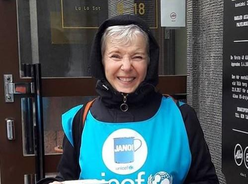 Nainen hymyilee, hänellä on päällä sininen Unicef-liivi