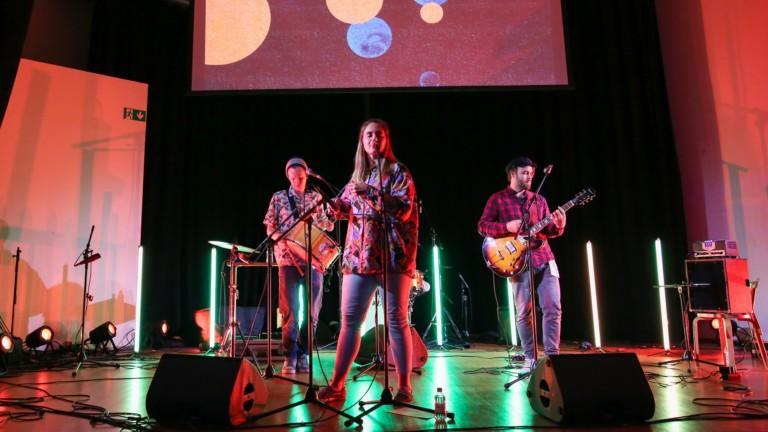 Kolmihenkinen bändi esiintyy lavalla.