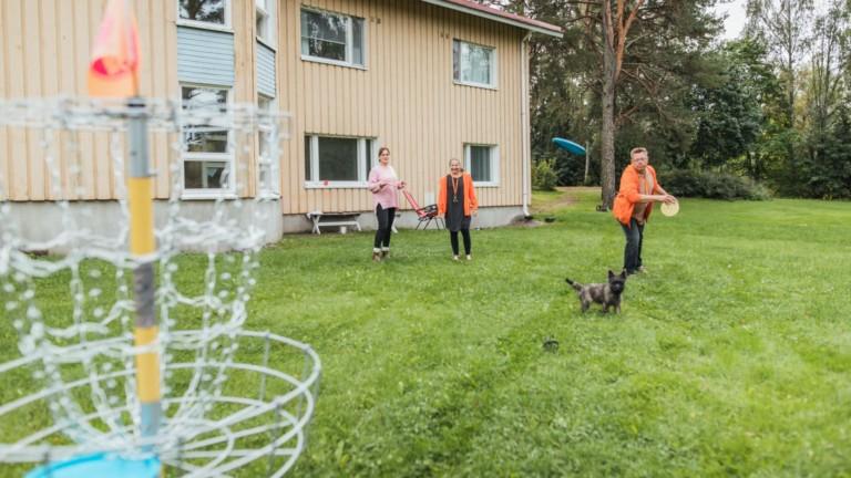 Kolme ihmistä on keltaisen talon pihalla heittämässä frisbeetä.