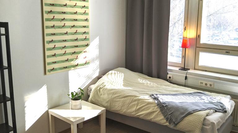 Makuuhuone, jossa on sänky, yöpöytä ja taulu seinällä.