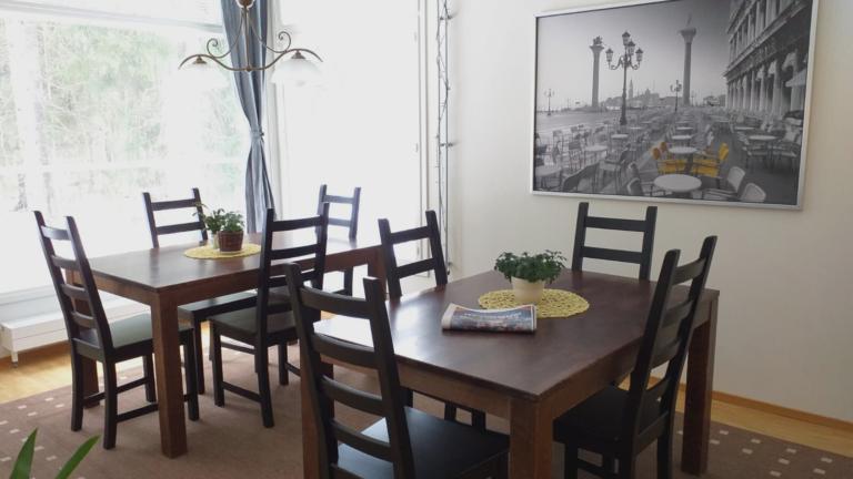 Ruokailutila, jossa on kaksi ruokapöytää tuoleineen.