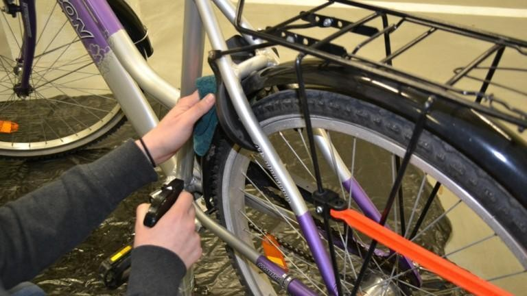 Henkilö puhdistaa pyöräänsä