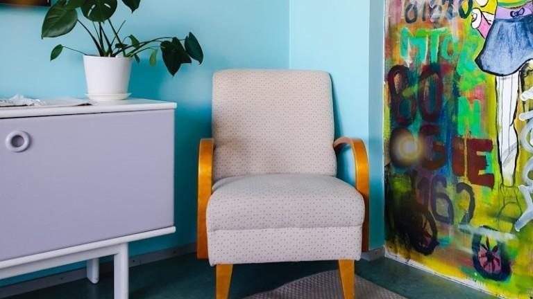 Nojatuoli huoneen nurkassa viherkasvin vieressä.