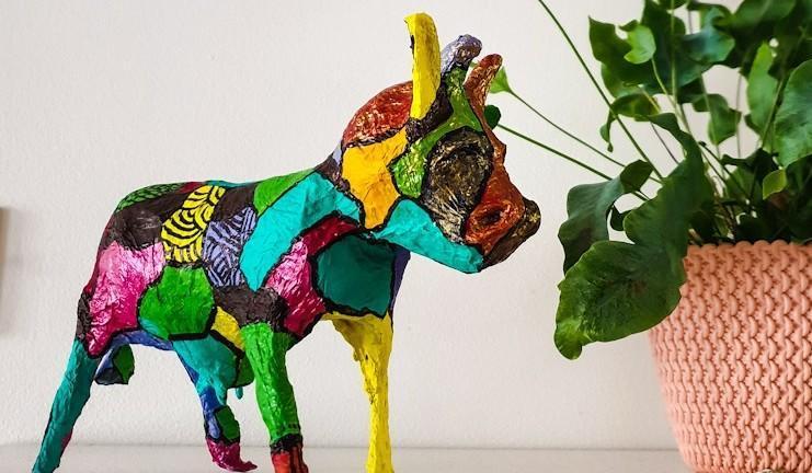 Eläinhahmoa esittävä koriste-esine viherkasvin vieressä.
