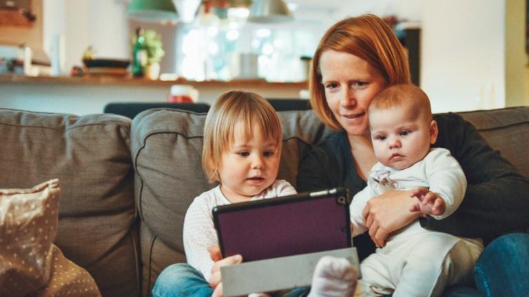 Äiti ja lapset katsovat tablettia