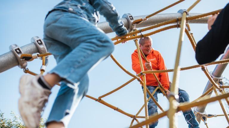 Lapsi ja aikuinen kiipeilevät kiipeilytelineessä.