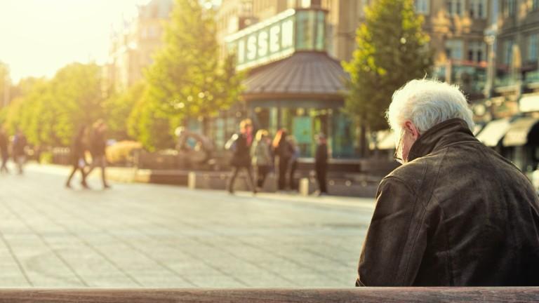 Vanhus istuu penkillä aukion laidalla.