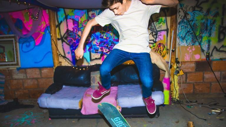 Mies tekee temppua rullalaudalla värikkäässä huoneessa.