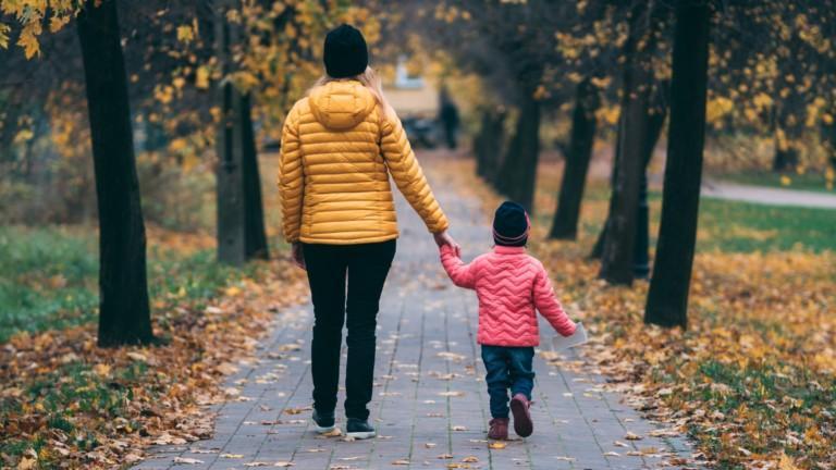 Nainen ja lapsi kävelevät käsi kädessä puiden keskellä, maahan on pudonnut paljon lehtiä.