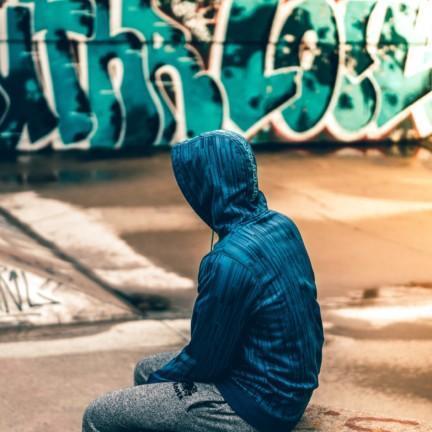 Nuori istuu graffitien edessä huppari päällä.